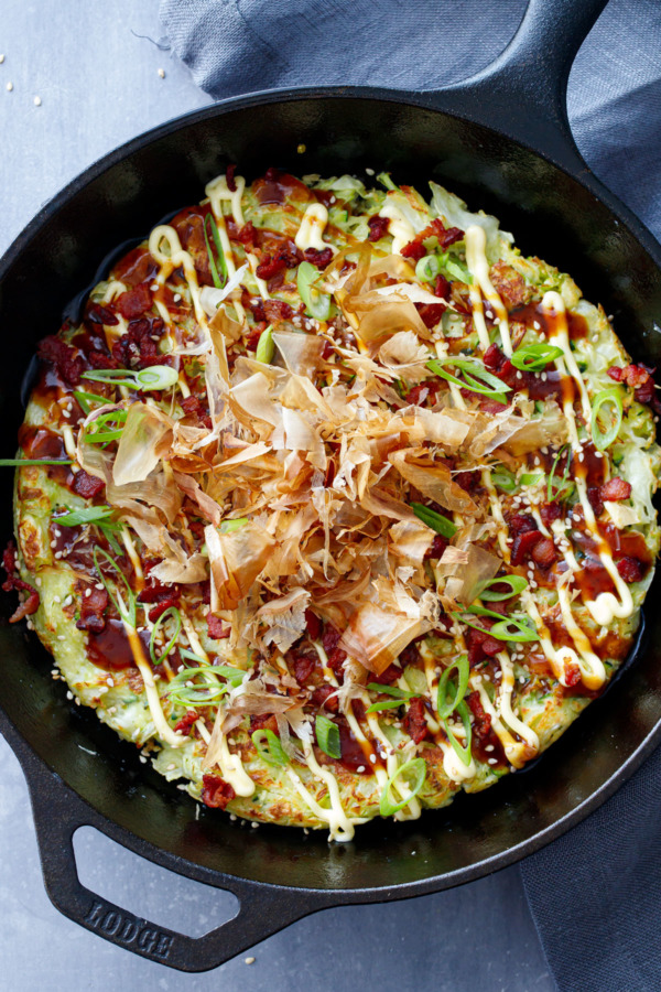 Overhead shot of cast iron skillet with okonomiyaki (Japanese Savory pancake), drizzled with sauce and topped with bonito flakes