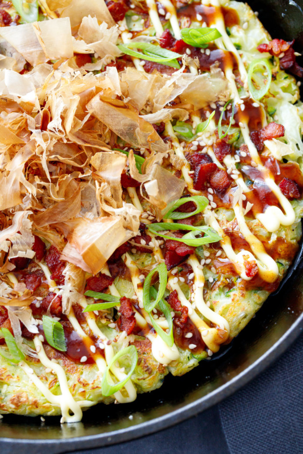 Close up of Cabbage & Zucchini Okonomiyaki cooked in a cast iron skillet, topped with bonito flakes.