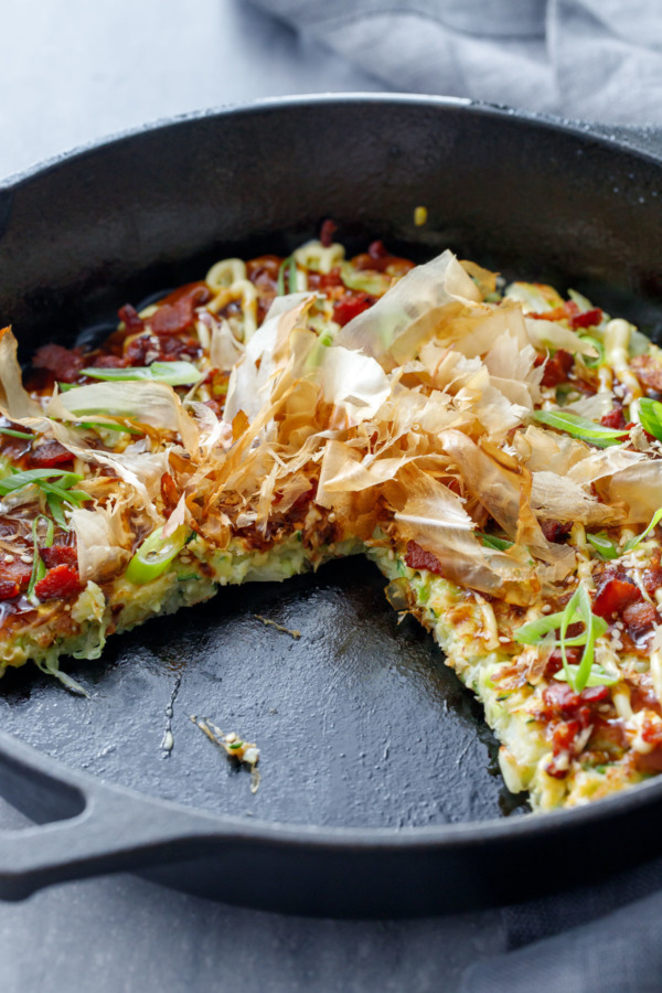 A cast iron skillet with Cabbage & Zucchini Okonomiyaki with a slice cut out of it.