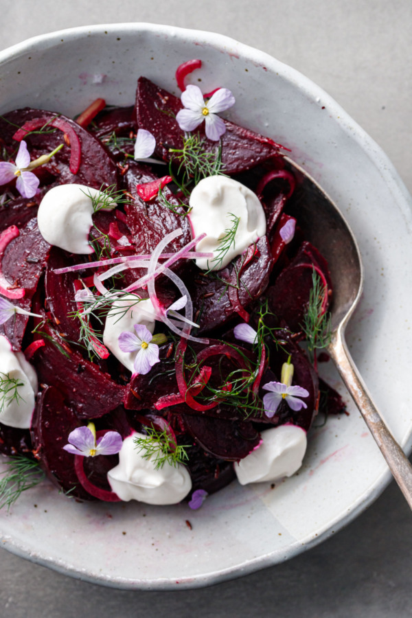 Closeup of a cumin-spiced beet salad, with dollops of greek yougurt, fresh dill and purple radish flowers scattered on top