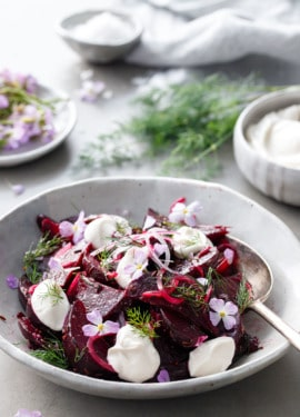 Handmade ceramic bowl filled with cumin-spiced beet salad with bowls of yogurt and radish flowers and fresh dill in the background
