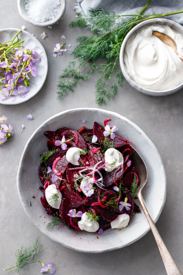 Overhead shot of cumin-spiced beet salad with bowls of yogurt and radish flowers on the side