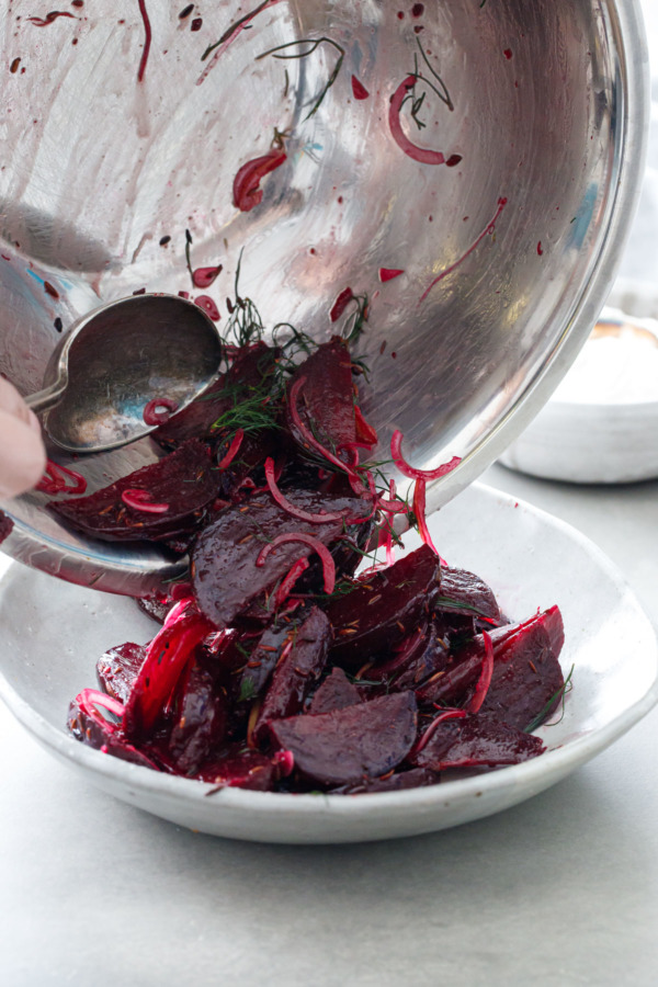 Beets tossed with spiced cumin oil, red onion and preserved lemon being poured into a serving bowl