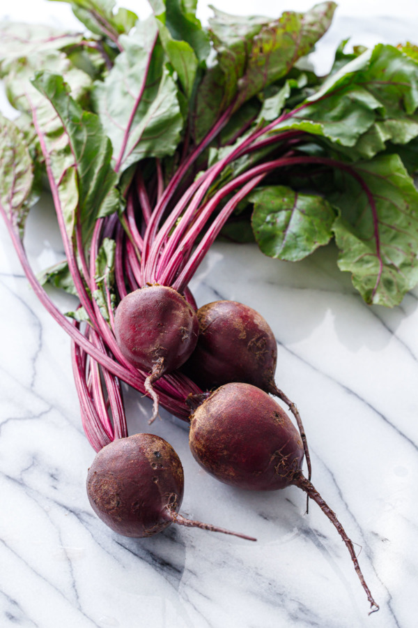 Bunch of fresh red beets with green leaves on a marble surface