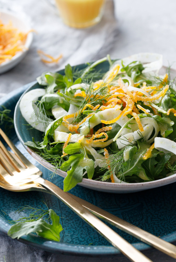 Fennel and Arugula Salad with Candied Orange Peel, served in a Handmade ceramic bowl with gold flatware.