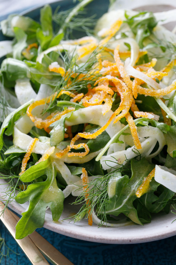 Close up shot of a bowl of Fennel and Arugula Salad with Candied Orange Peel and drizzled with orange vinaigrette.