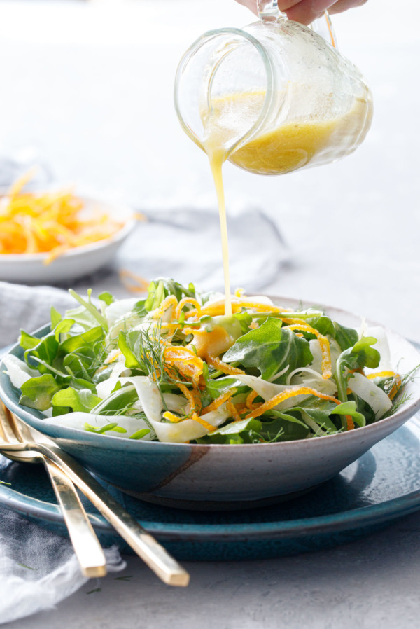 Drizzling an orange vinaigrette dressing onto a bowl of arugula fennel salad, dish of candied orange peel in the background.