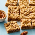 Dulce de Leche Oatmeal Crumb Bars on a blue background with a bowl and spoon of dulce de leche