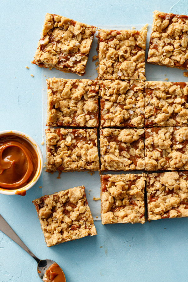 Overhead sot of Dulce de Leche Oatmeal Crumb Bars, cut into squares on a light blue background