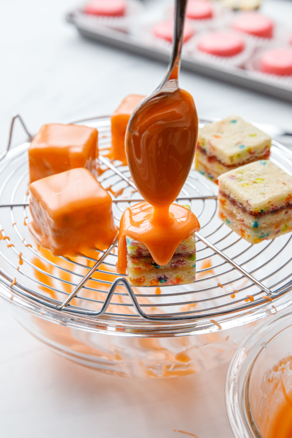 Glazing individual petit fours cakes with an orange colored poured fondant glaze.