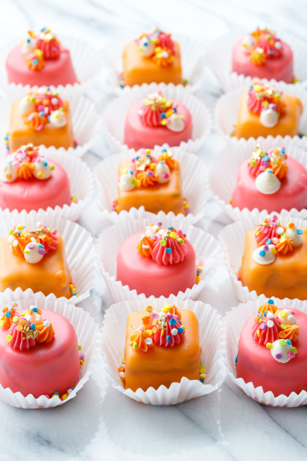 """Rows of pink and orange """"Funfetti Fours"""" with buttercream decorations and rainbow sprinkles"""
