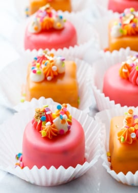 "Rows of pink and orange ""Funfetti Fours"" with buttercream decorations and rainbow sprinkles"