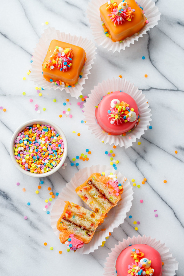 """Overhead view of pink and orange """"funfetti fours"""", one cake cut in half to show the apricot and raspberry jam layers, with a bowl of rainbow sprinkles."""
