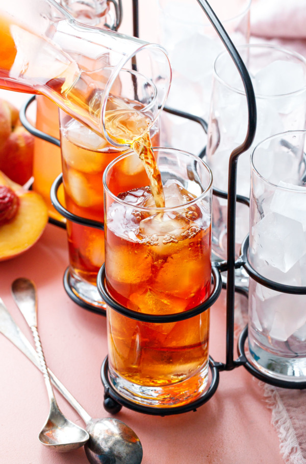 Pouring Cold Brew Peach Iced Tea into a glass filled with ice