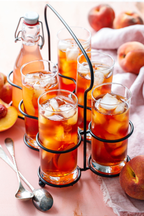 A vintage drink caddy with 5 glasses of Cold Brew Peach Iced Tea, and one bottle of peach sugar syrup