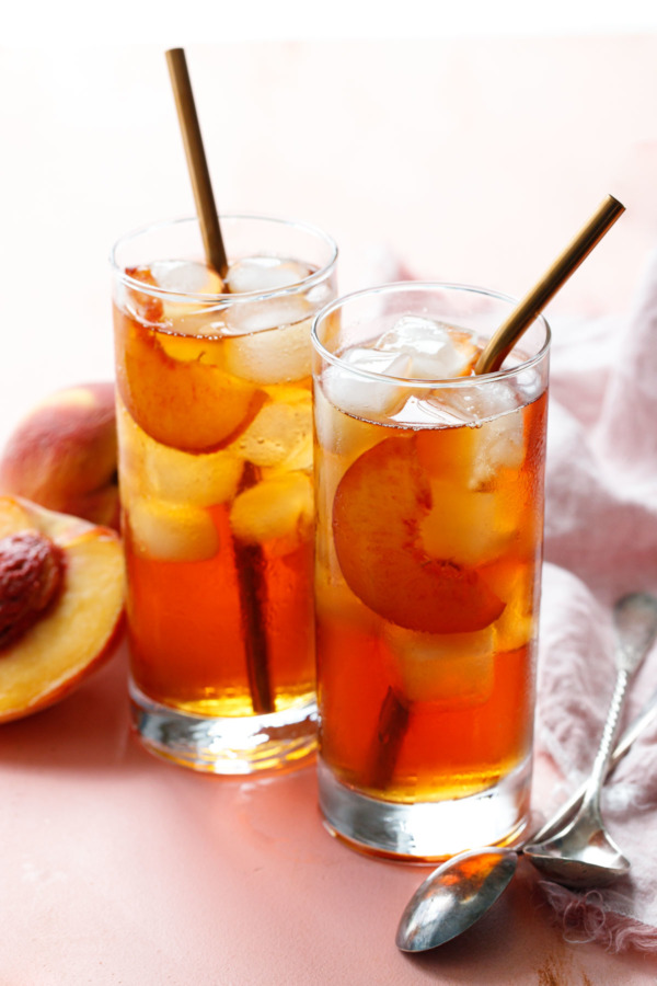 Two glasses filled with Cold Brew Peach Iced Tea, with rose gold metal drinking straws and fresh peaches on the side.