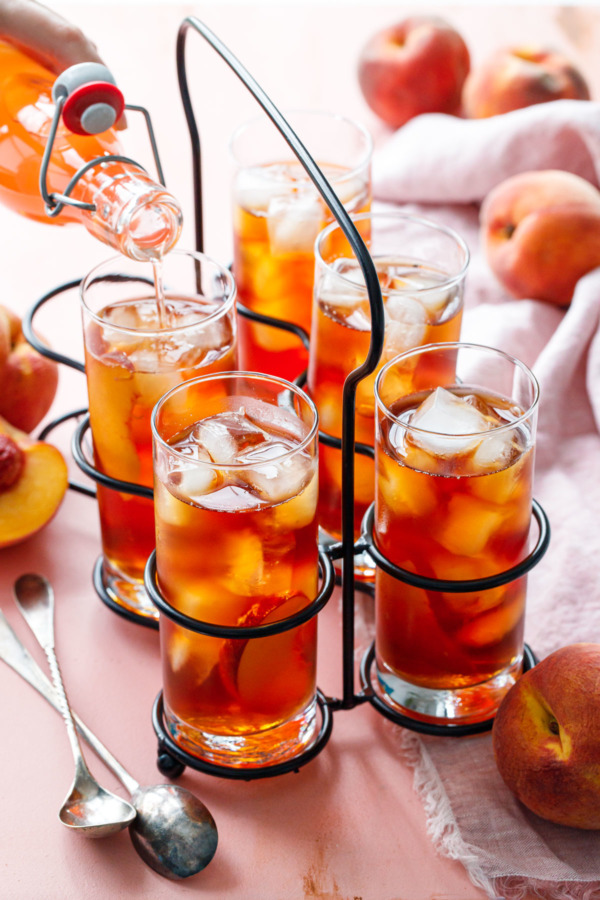 A vintage drink caddy with 5 glasses of Cold Brew Peach Iced Tea, and one bottle of peach sugar syrup being poured into one of the glasses.