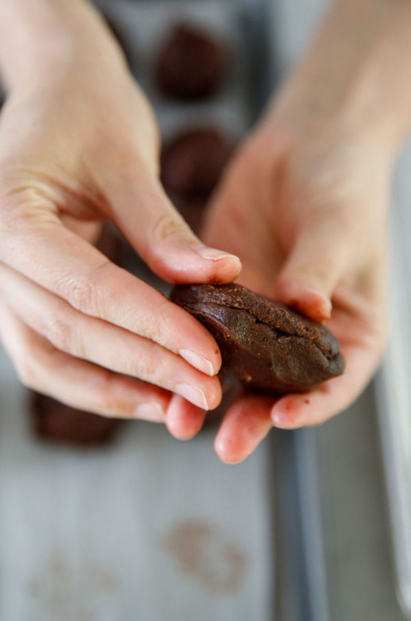 How to stuff a chocolate cookie with white chocolate: seal the edges of the dough and roll into a puck-shape.