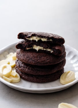 Stack of White Chocolate-Stuffed Chocolate Cookies, top cookie broken in half to show the melted white chocolate center.