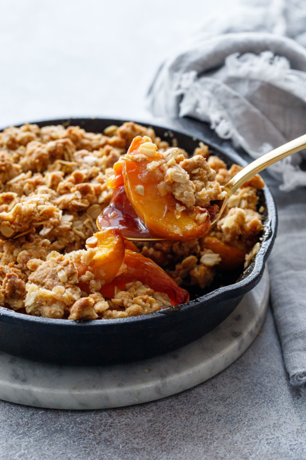 A serving spoon scooping a heaping serving of Skillet Bourbon Peach Crisp out of a cast iron skillet