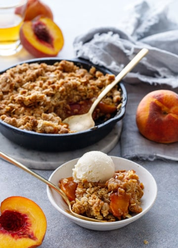 Skillet Bourbon Peach Crisp with fresh peaches on the side and a shot glass of bourbon.
