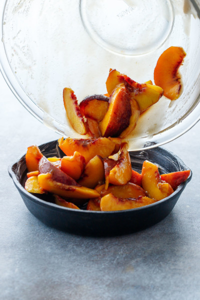 Pouring macerated sliced peaches into a cast iron skillet to make Bourbon Peach Crisp