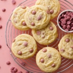 Overhead shot of Cacao Butter and Ruby Chocolate Chip Cookies on a wire rack with a dish filled with ruby cacao wafers, pink background.
