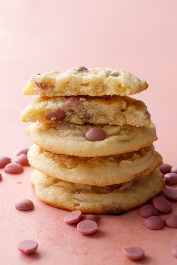 Stack of Cacao Butter and Ruby Chocolate Chip Cookie on a pink background, one cookie broken in half to show the texture inside.