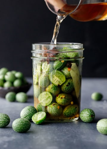 Pouring the cider vinegar-based brine into a jar packed with cucamelons.