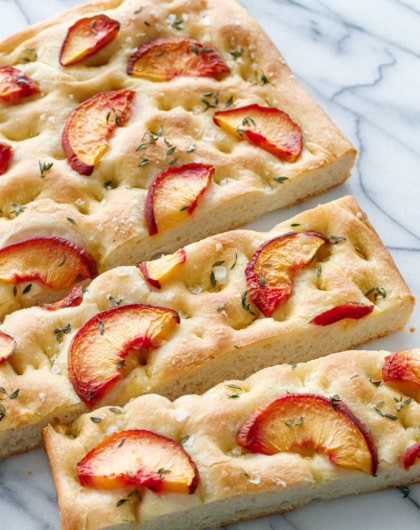 Peach & Fresh Herb Focaccia Bread on a marble background cut into slices
