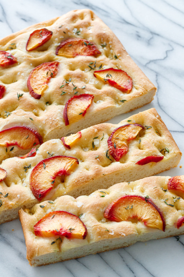 Peach & Thyme Focaccia Bread on a marble background cut into slices