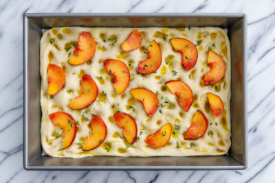 How to make homemade focaccia bread: top with a generous drizzle of olive oil, sliced peaches, fresh herbs and coarse sea salt.