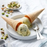 Two cones of pistachio gelato overturned on a white plate with two spoons and dish of green pistachios on the side.