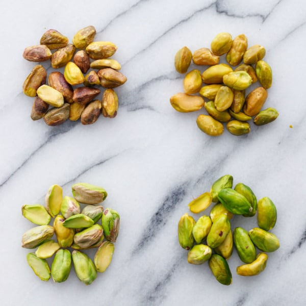 Comparison shot showing pre-peeled pistachios (raw and blanched) and pistachios that have been freshly shelled (raw and blanched/peeled).