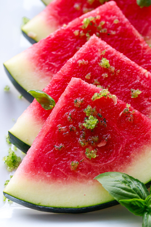 Closeup of watermelon slices, sprinkled with basil lime sugar