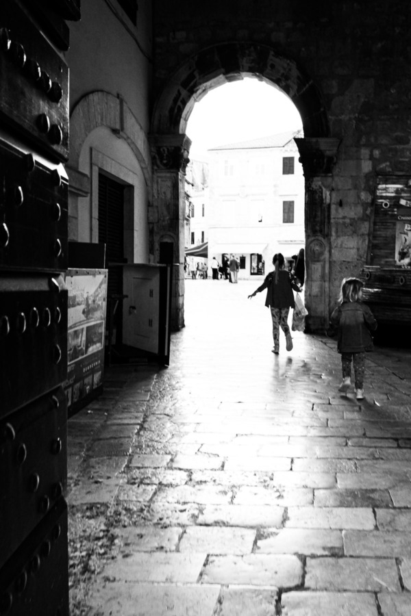 Little girls running through an archway in Dubrovnik, Croatia