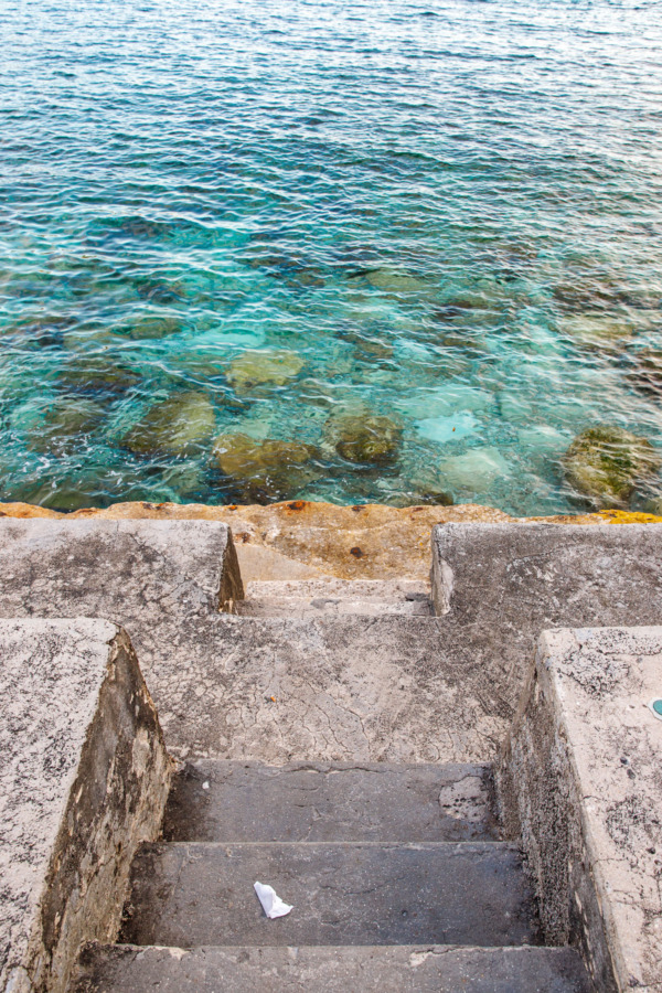 Stairs leading town to vibrant turquoise water in Dubrovnik, Croatia