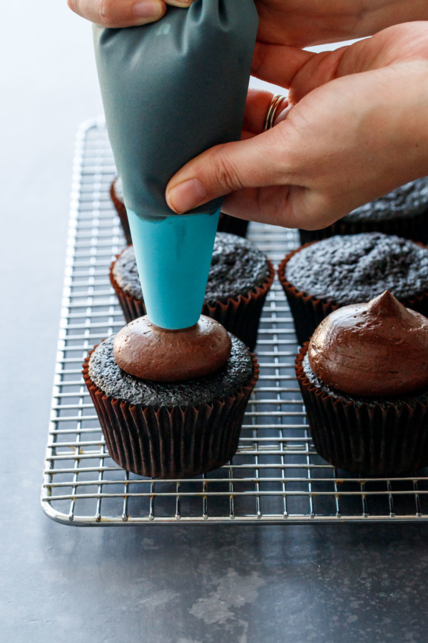 Piping chocolate fudge frosting onto the Ultimate chocolate cupcakes