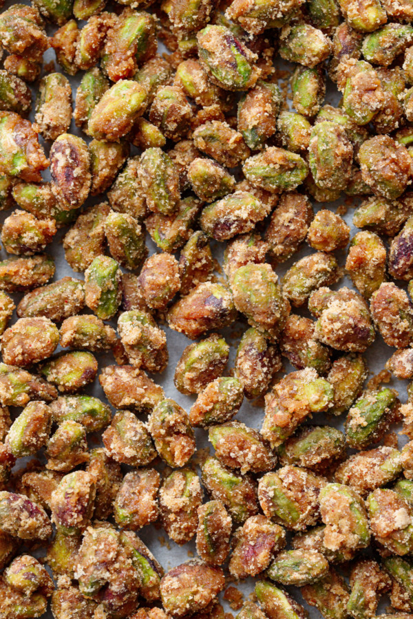 Closeup textural of spiced candied pistachios on a baking sheet.