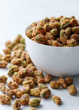 A white porcelain bowl overflowing with spiced candied pistachios on a marble surface