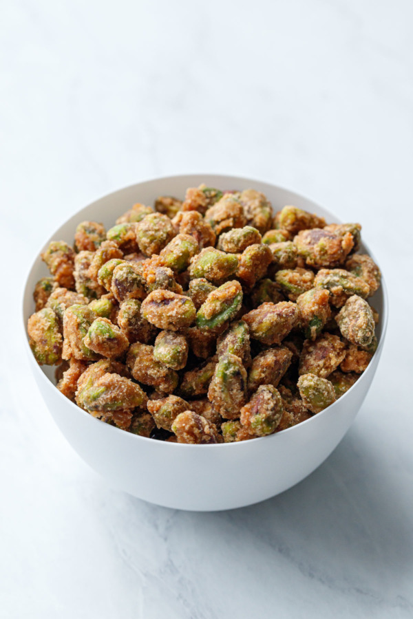 A white porcelain bowl full of spiced candied pistachios