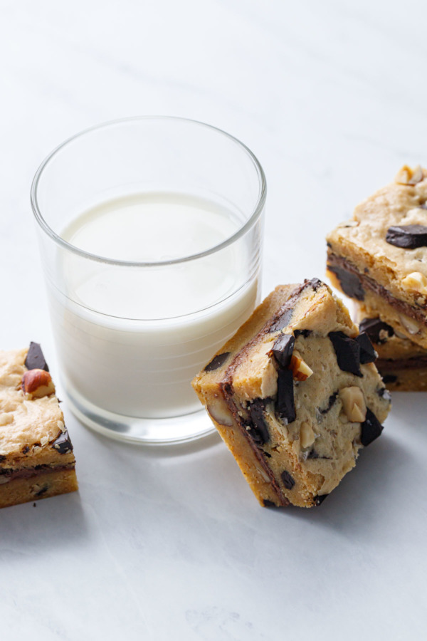 Square cut blondies on a white marble background, one leaning against a glass of milk.