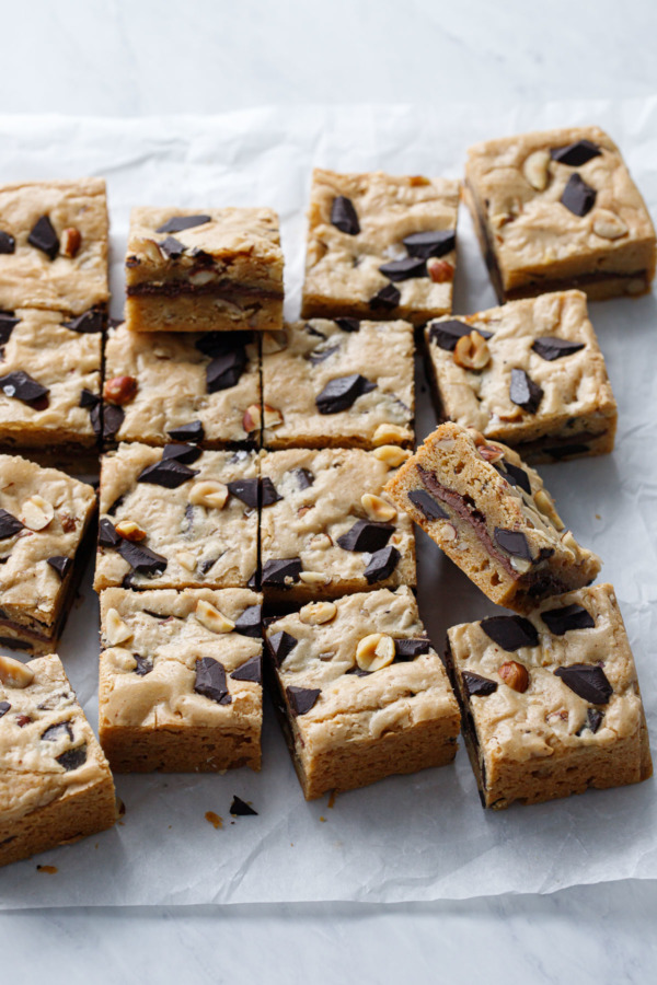 Nutella-Stuffed Brown Butter Blondies cut into squares on parchment paper background