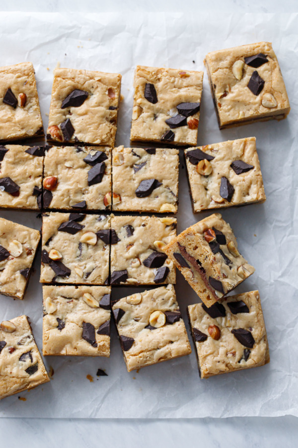Overhead shot of Nutella-Stuffed Brown Butter Blondies cut into squares on a crinkled parchment paper background