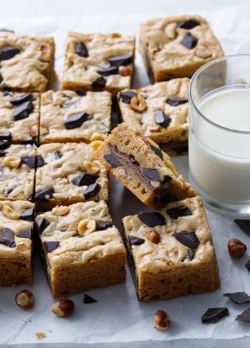 Nutella-Stuffed Brown Butter Blondies cut into squares with a glass of milk on the side.
