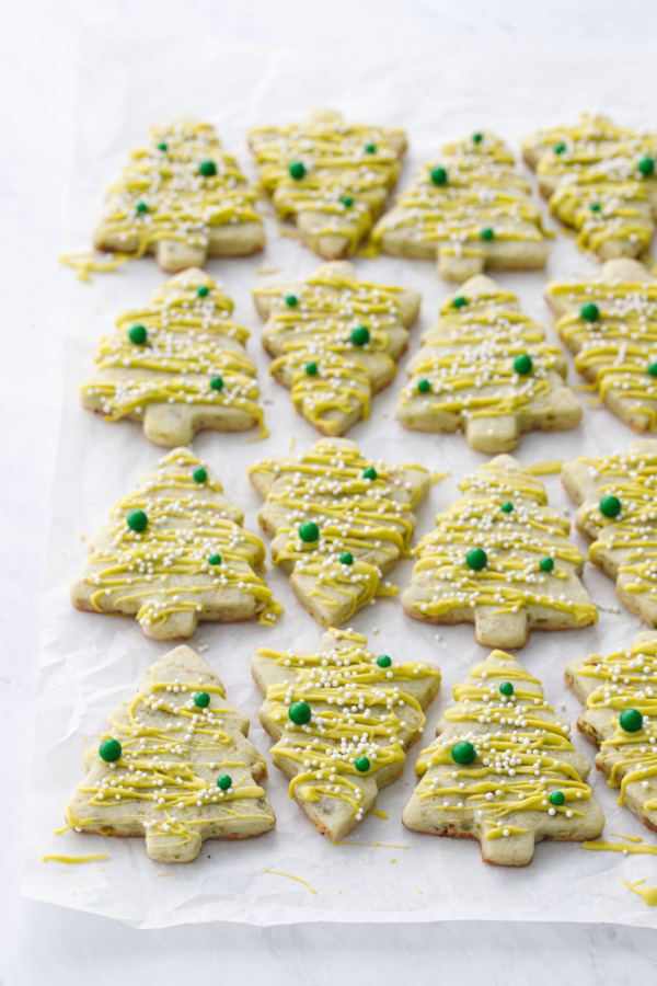 Tree-shaped pistachio sugar cookies arranged on a crinkled piece of parchment