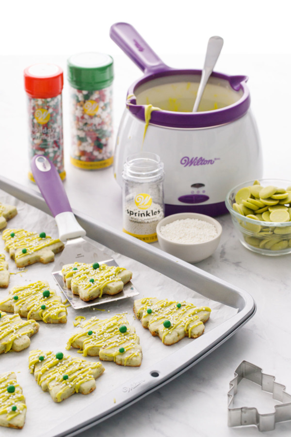 Cookie sheet with pistachio cutout cookies and the various Wilton tools used to make and decorate them.