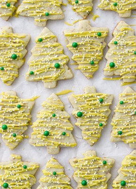 Alternating tree-shaped pistachio cut out cookies on parchment paper