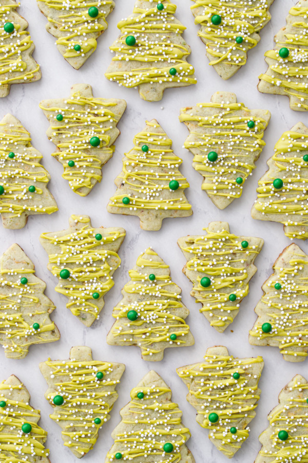 Alternating rows of pistachio Christmas tree cookies on a marble background