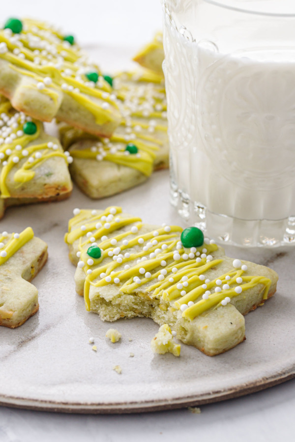 A pistachio Christmas tree cookie with a bite out of it, on a plate with a glass of milk in the background.
